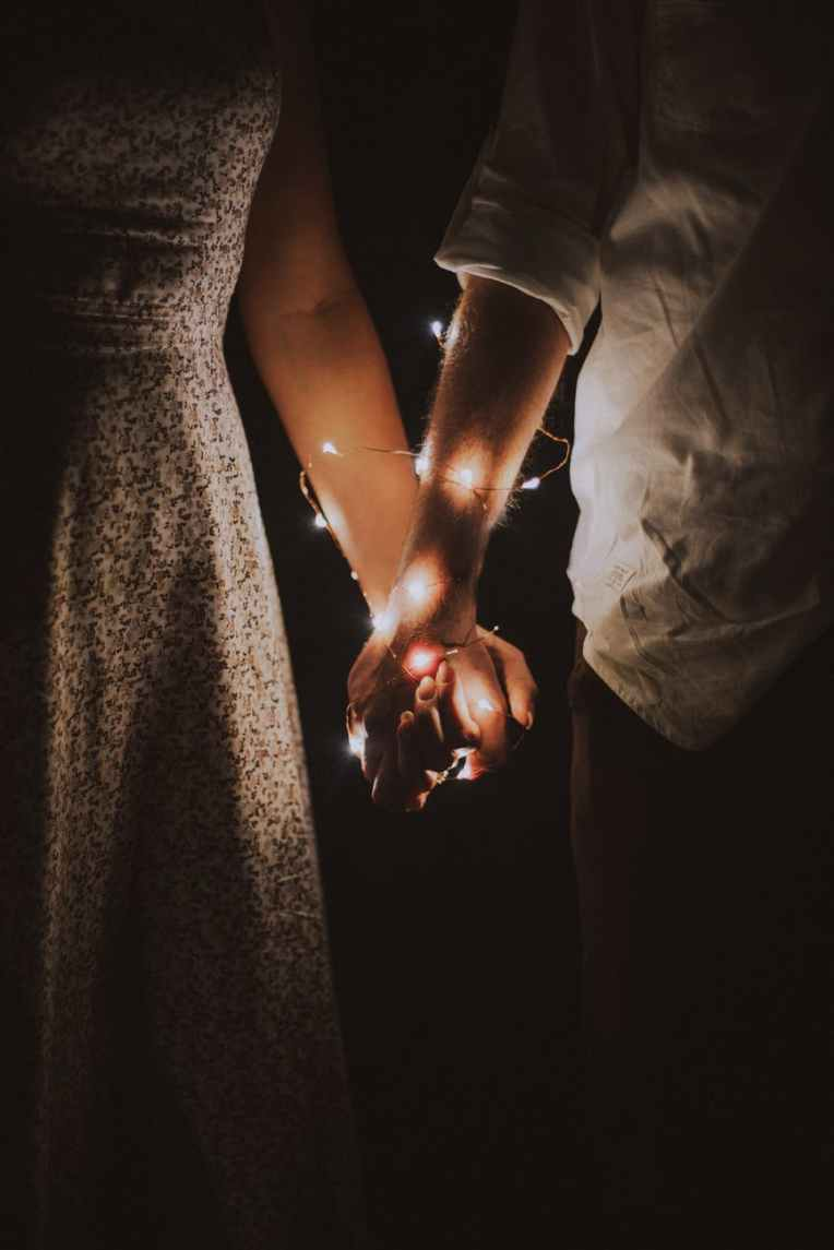 man and woman holding each others hand wrapped with string lights