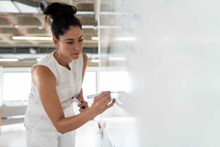woman in white sleeveless top writing on a whiteboard
