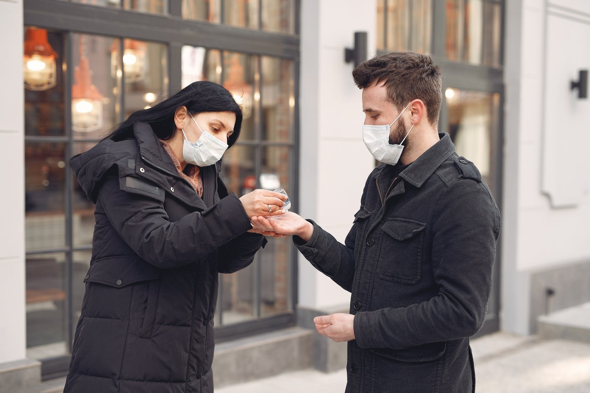 woman putting hand sanitizer on man s hand