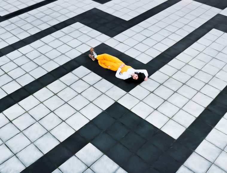 woman in yellow pants lying on concrete tiled floor